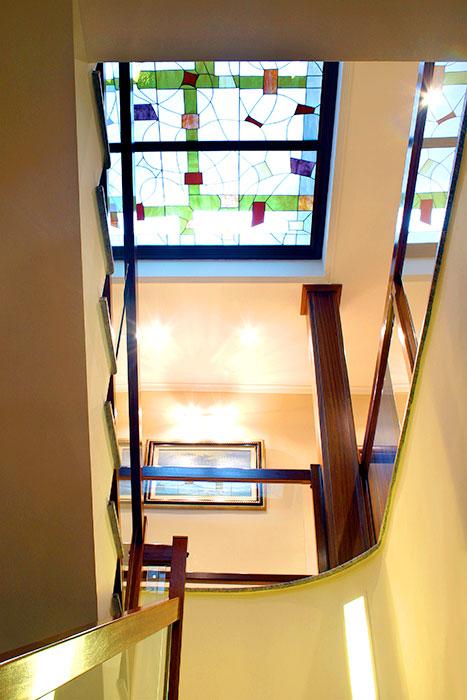 vista desde abajo de escalera con barandilla de madera con cristal y vista de claraboya